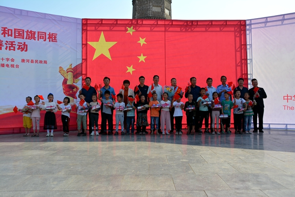 """唐河县举行""""我爱我的祖国 我和国旗同框""""公益慈善捐助暨共庆新中国成立70周年主题活动 中国财经新闻网 www.prcfe.com"""